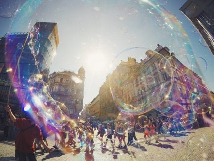 City scene with bubbles in foreground and kids walking in background
