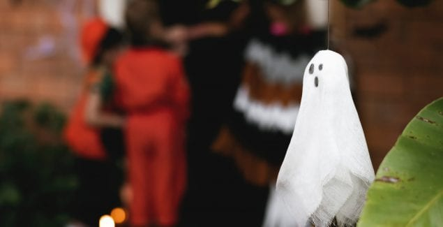 Ghost decoration in foreground of kids trick-or-treating