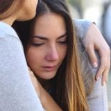crying teen being held by friend after disclosing sexual assault