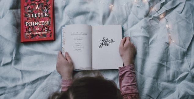 Child holding open a story book, surrounded by magical lighting