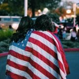 Two individuals walking with backs to camera, draped in American flag