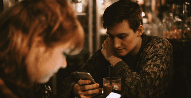 Two teens checking their phones