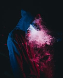 Hooded teenager in front of black background standing amidst pink vapor from e-cigarette