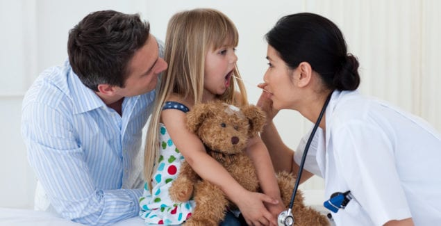 Doctor examining child's throat during a check-up, with parent in the room