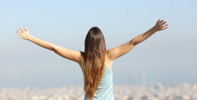 Back view of a happy tourist woman raising arms looking at the city landscape