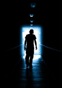Silhouette teen boy with head down, in dark hallway walking toward the light