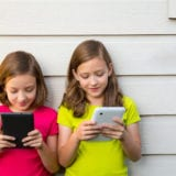 Twin sister girls playing with tablet pc happy on white wall looking screen