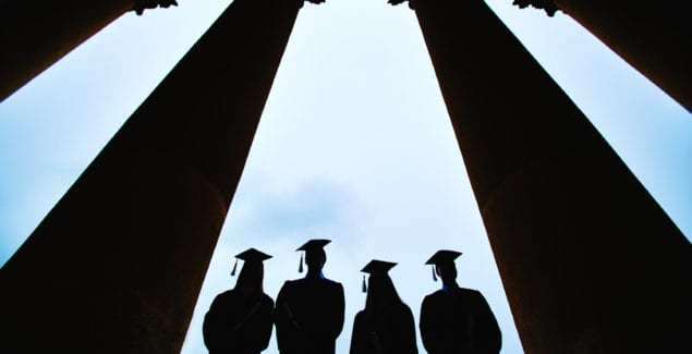 Image of 4 college student grads with commencement caps on in silhouette