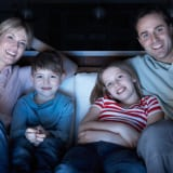 Family Watching TV On Sofa Together