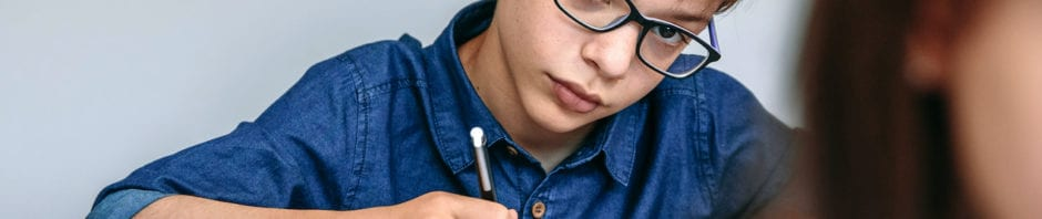 Teen writing in his notebook at school.