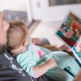Father reading a book to baby at bedtime