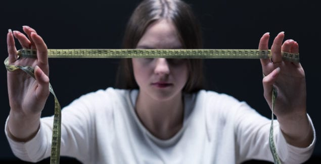 Teen girl in shadows stretching out tape measure in front of her face