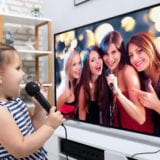 Girl standing in front of TV singing with microphone