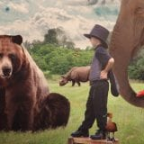 Young child wearing top hat in land of make believe surrounded by large animals - bear, elephant, zebra