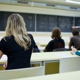 behind shot of female college student sitting in a classroom full of students during class