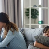 Angry sulky child girl and annoyed mother sitting back to back on sofa not talking after fight