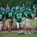 Teenagers on a football team wait for their turn on the field