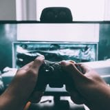 person holding game controller in-front of television