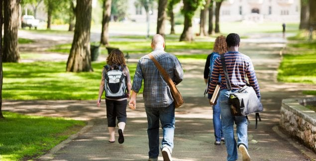 University students with backpacks walking on campus road