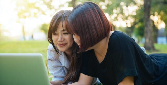 Two Asian women lying in the grass together looking at a laptop
