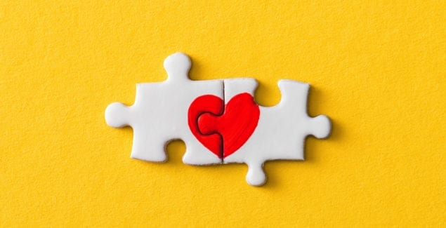 at-risk emotions, connected heart jigsaw puzzle pieces over yellow background