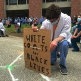 "Healthcare worker kneeling with a sign that says ""White coats for Black Lives Matter"""