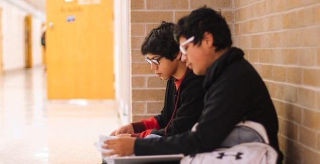 Two Latinx boys sitting in a school hallway together