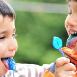 Two boys eating bright blue lollipops
