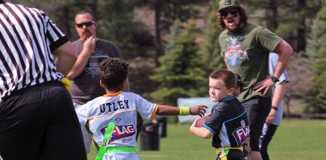 Parents shouting from sidelines at flag football game for 5 and 6 year old athletes