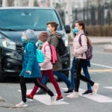 Kids walking across the street to school while wearing masks