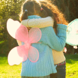 Behind shot of two children wearing fairy wings hugging each other
