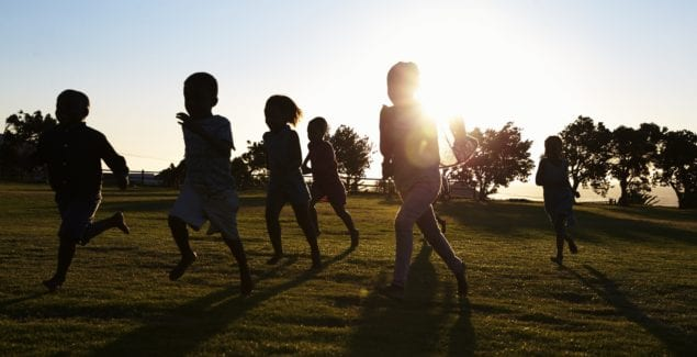 Silhouetted elementary school kids running in a field