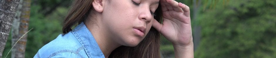 Distraught teen girl, with eyes closed and hand to head