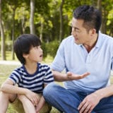 Asian father and son sitting and talking outside