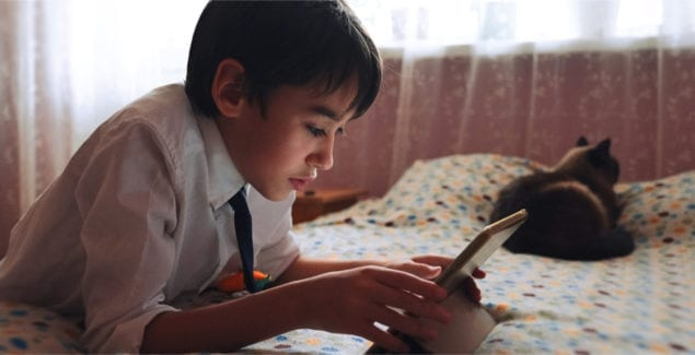 A young teen boy in a white shirt with a tie uses a tablet to communicate in video chat, in his bedroom, with a cat by his side.