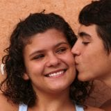 Young teen girl smiling while young teen boy kisses her cheek