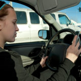 Girl texting with cell phone while driving, hand on steering wheel
