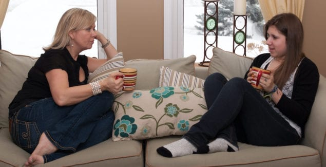 Mother and teenage daughter talking and sitting on a couch