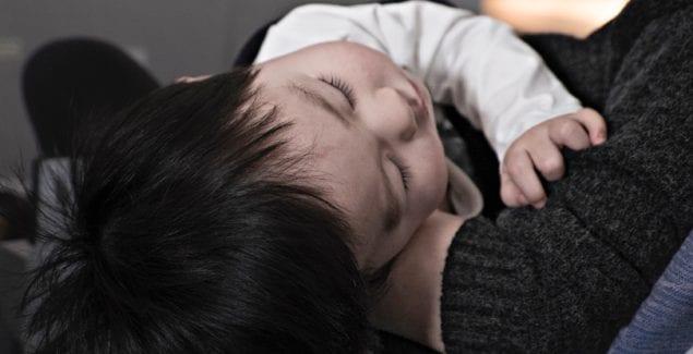Young toddler asleep on parent's lap