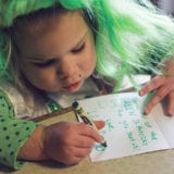 Toddler wearing a green wig while writing a thank you note