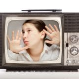 Girl trapped inside a retro portable TV over white background