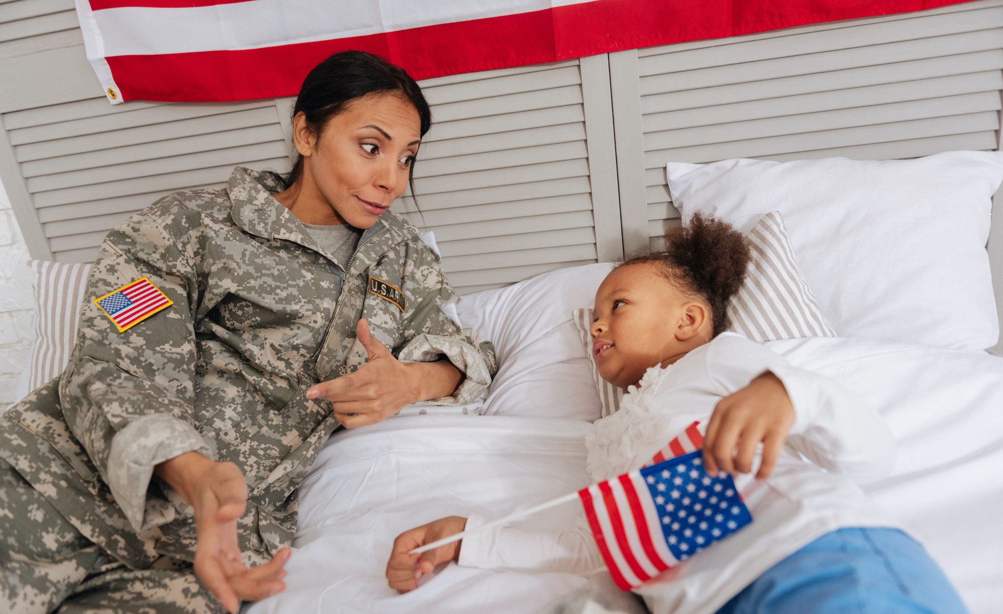 Veteran mother having a conversation with her daughter on a bed
