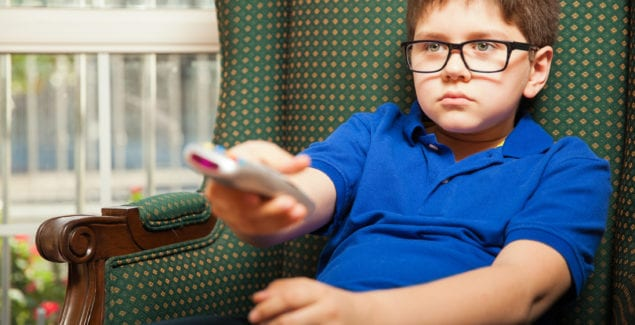 Young male child sitting leaning back on sofa flipping through channels