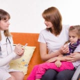 Female doctor sits on a couch next to mother holding sick young girl with thermometer in her mouth