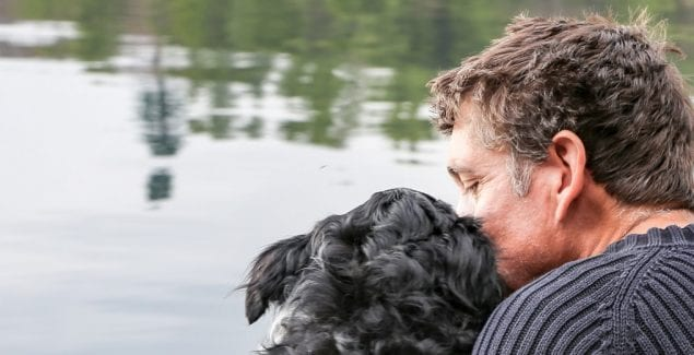 Behind view of man and dog sitting and hugging in front of lake