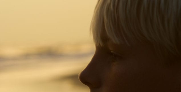 Profile of caucasian pre-teen boy on beach at sunset.