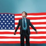 Image of a young child dressed in business suit looking authoritarian while standing in front of American flag backdrop