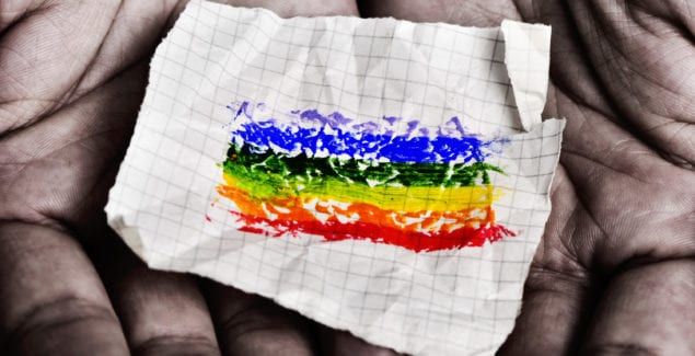 closeup of a young caucasian man with a piece of paper in his hands with a rainbow flag painted in it