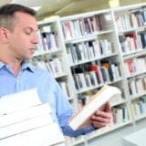Middle-aged man reads back cover of book while holding stack of books in one arm