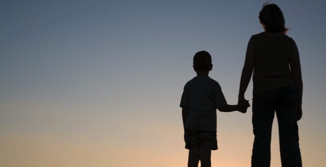 Silhouettes of mother and son at sunset